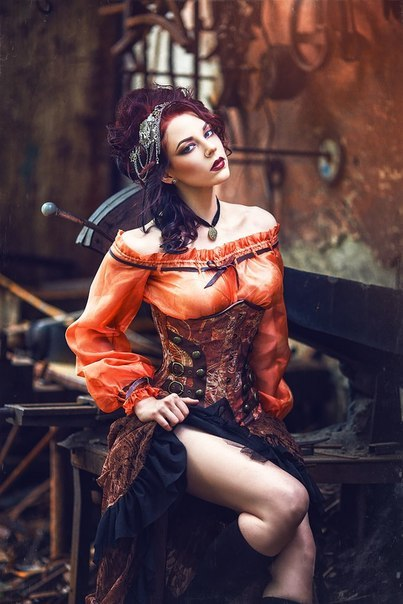 Women's steampunk clothing. Orange, brown and black outfit for fall fashion/autumn style. Peasant blouse, corset, high low skirt and jewelry headpiece.