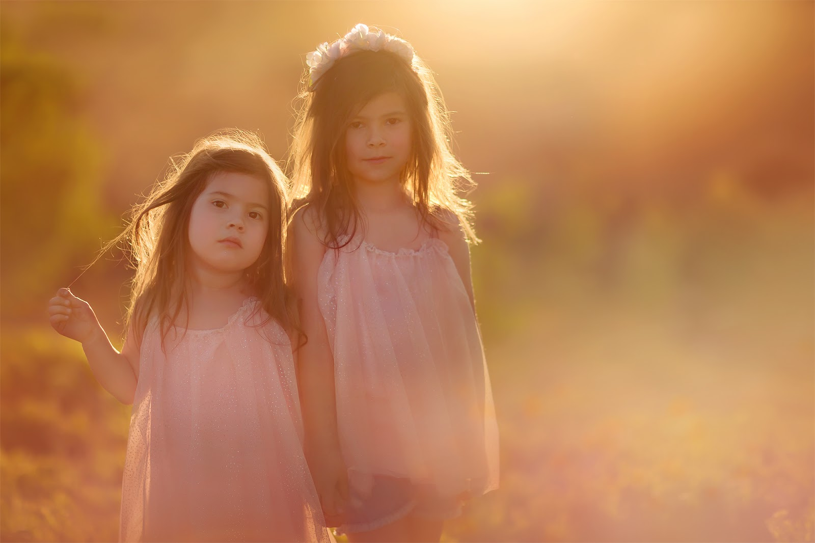 Canon color fine art portrait of two little sisters posing in front of a camera during sunset by Willie Kers