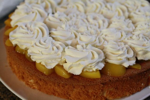 torta esponja, con una capa de duraznos y crema encima