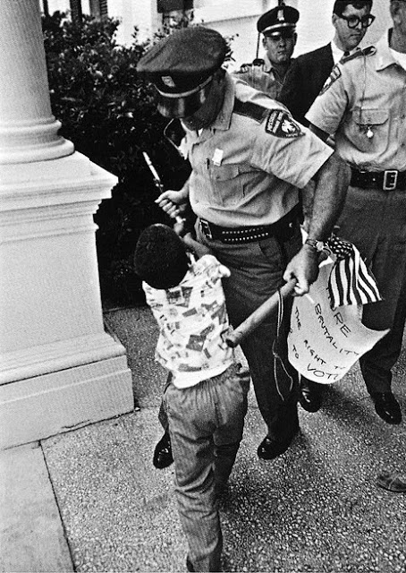U.S. Highway patrolman Huey Krohn pulls away a small American flag from five-year-old boy Anthony Quinn during a civil rights protest. 1965. Photo by Matt Herron