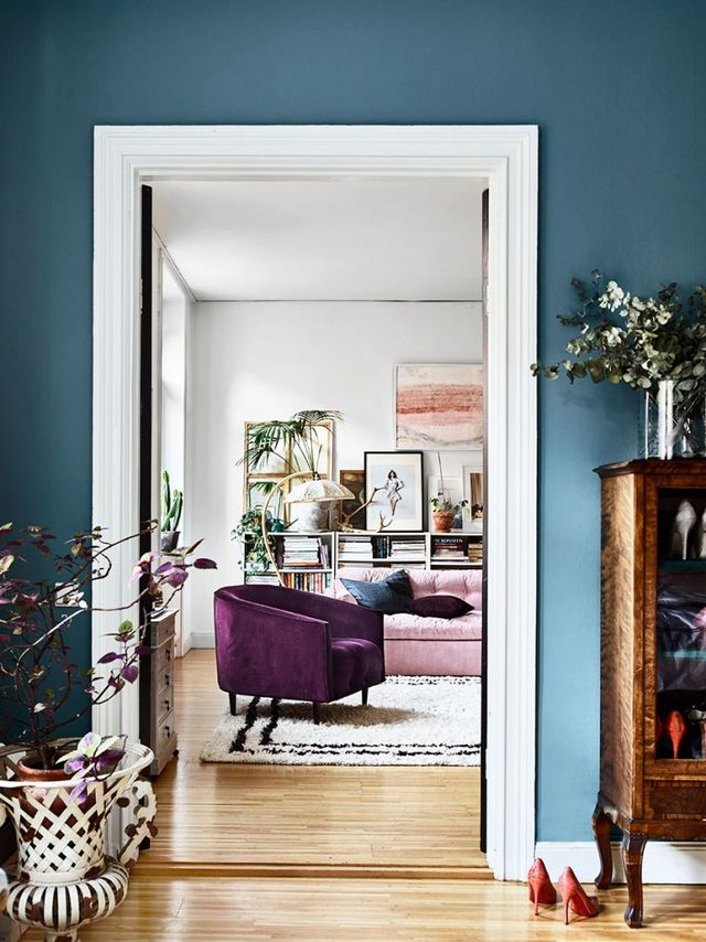eclectic livign room, purple chair, houseplants, flowers in interior,