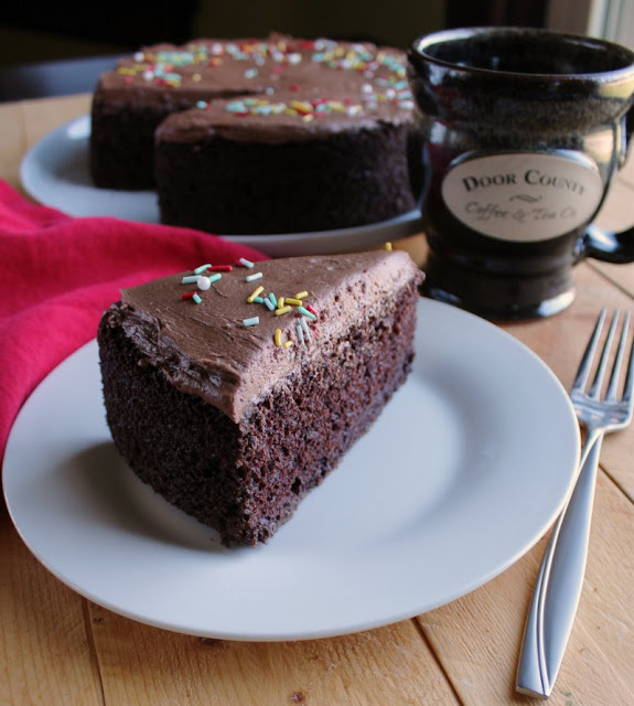 slice of chocolate cake with remaining cake and coffee cup in the background