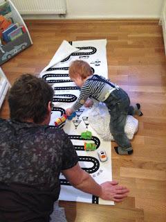 Papa und Sohn spielen mit den Tut Tut Autos auf einer Spielstraße