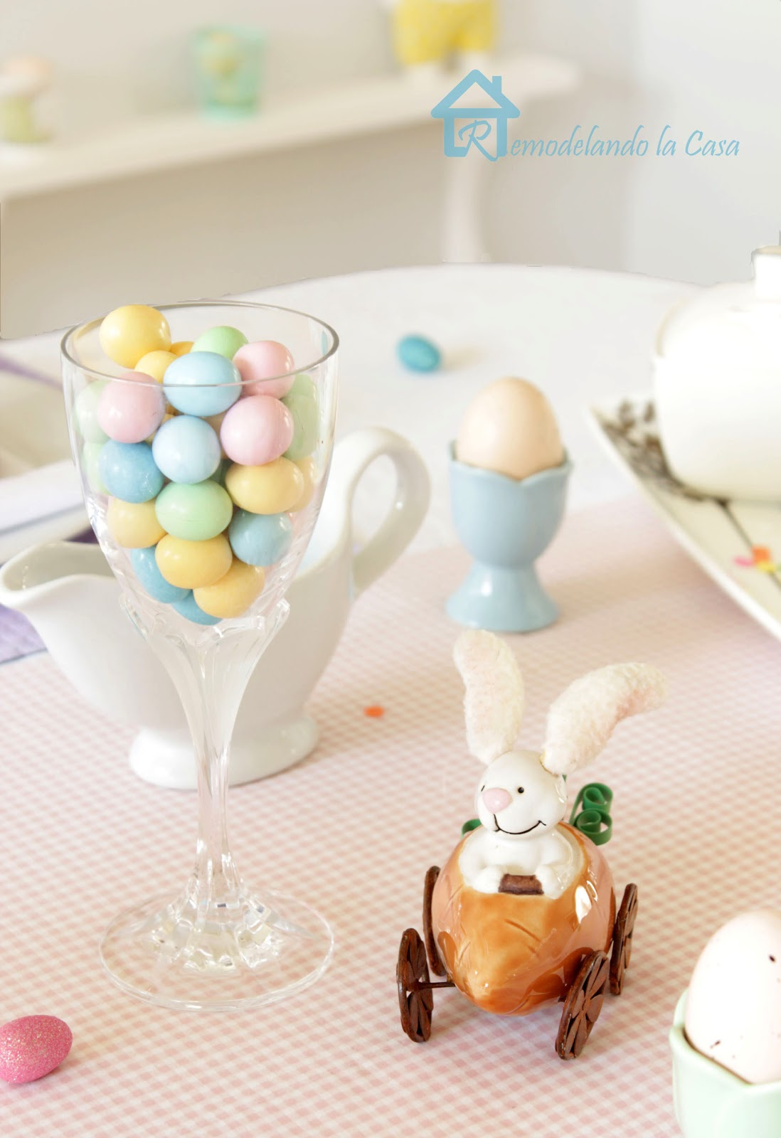 Easter tablescape with bunny in carrot car, glass full of candies