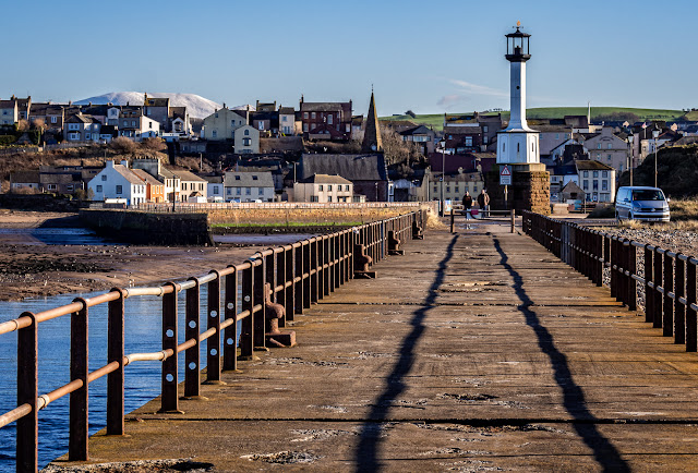 Photo of looking back along south pier at Maryport towards the town