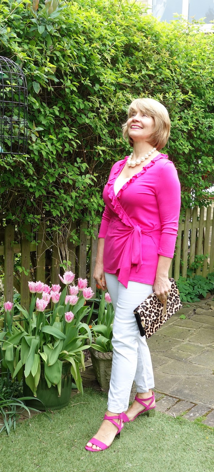 Wearing fuchsia pink top and sandals with an animal print clutch and pink tulips