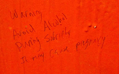 Graffiti on a red wall reading Alcohol consumed during sobriety causes pregnancy