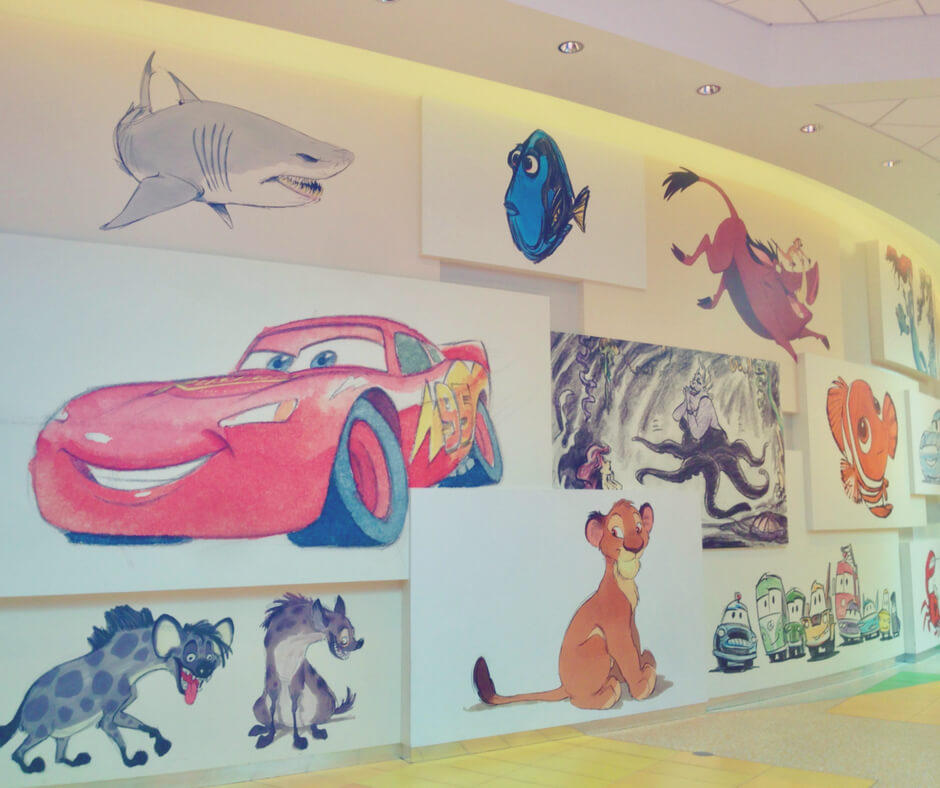An art wall showing drawings of Lightening McQueen, Dory, and Simba, at Art of Animation hotel in Walt Disney World.