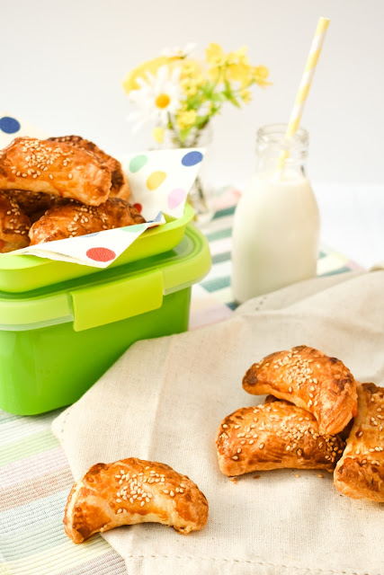 Mini Bean and Cheese Puff Parcels topped with sesame seeds in a lunchbox