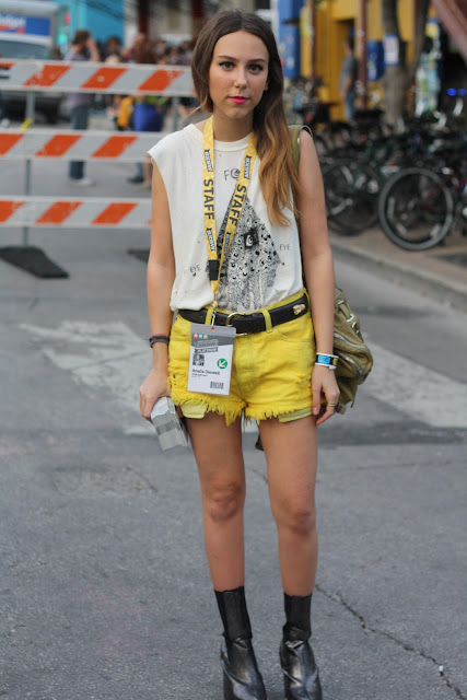girl wearing white tshirt and yellow cutoff shorts