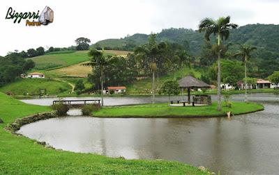 Construção do lago em sítio em Nazaré Paulista-SP com os muros de pedra rústica com a ponte de pedra e o quiosque de piaçava.