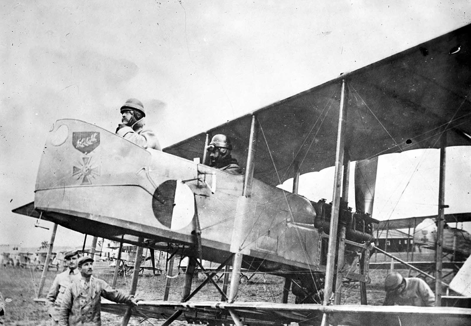 Captain Maurice Happe, rear seat, commander of French squadron MF 29, seated in his Farman MF.11 Shorthorn bomber with a Captain Berthaut. The plane bears the insignia of the first unit, a Croix de Guerre, ca. 1915.