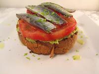 Tostada con aguacate, tomate y sardinas marinada cítrica.