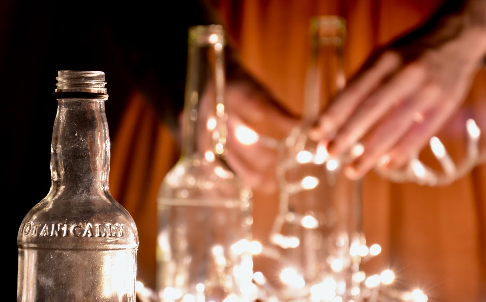 Empty bottles and Fairy Lights with Person in Background
