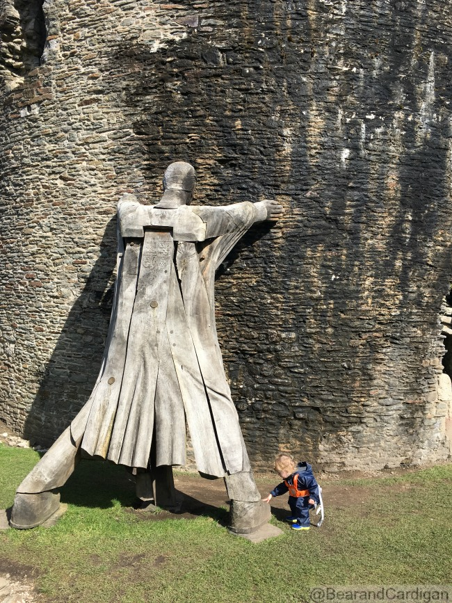 Caerphilly-Castle-with-toddler-crouching-next-to-giant-wooden-statue-holding-up-leaning-tower