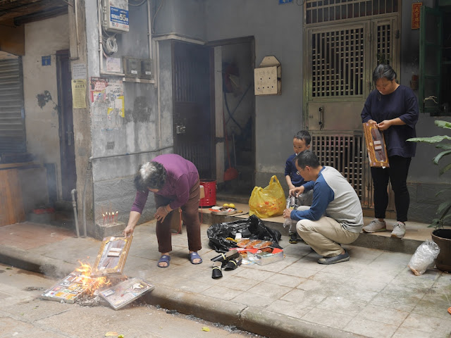 family burning paper replicas of items during Qingming