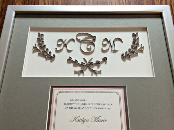 detail of a gray quilled wedding invitation mat in silver metallic smooth wood frame