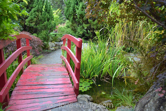 Red foot bridge leads us into the Japanese Gardens