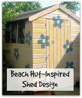 A Pink and Yellow Striped Shed with Large Blue Painted Flowers