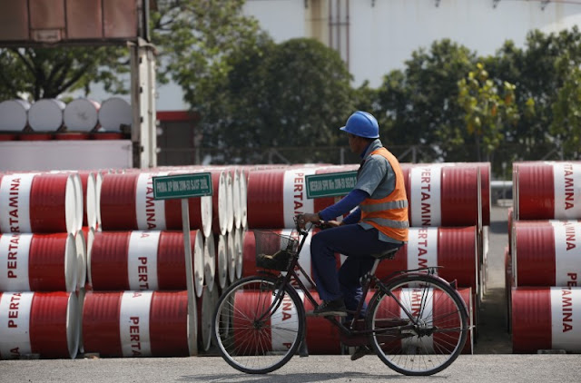 Image Attribute:  An employee rides his bike past barrels of petroleum products at a state-owned Pertamina fuel depot in Jakarta September 9, 2014. REUTERS/Darren Whiteside