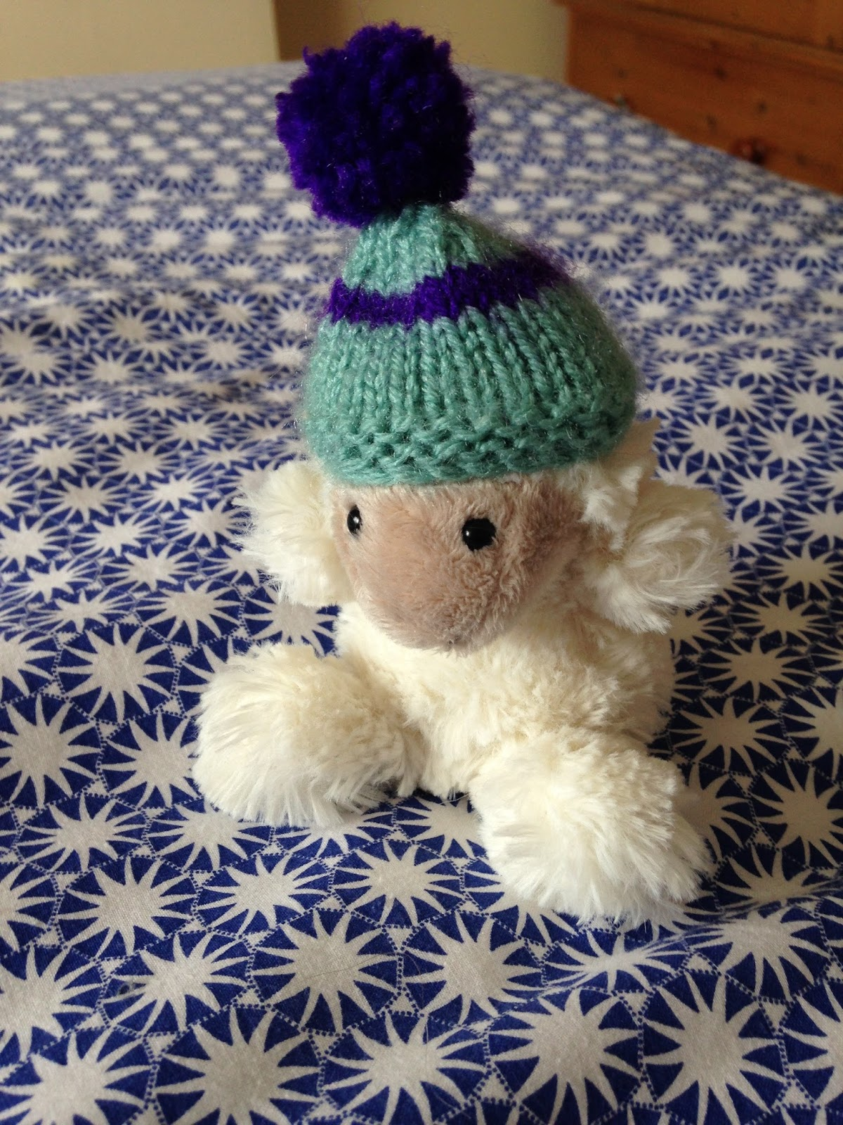 Small teddy on a bed wearing a hat
