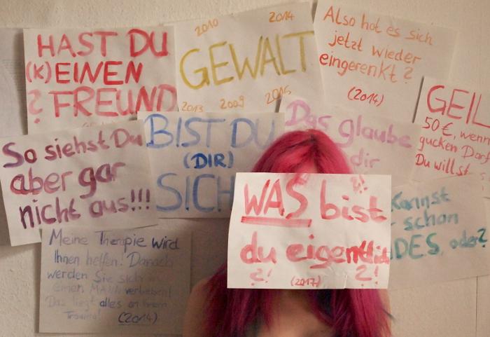 Zettel an der Wand mit Aufschriften: Hast Du (k)einen Freund?, Gewalt (2009, 2010, 2013, 2014, 2016), Also hat sich das wieder eingerenkt?, So siehst Du aber gar nicht aus!!!, Bist Du (Dir) sicher?, Du kannst aber schon beides, oder?, WAS bist Du eigentlich?