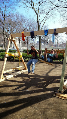 two people playing on wooden swingset