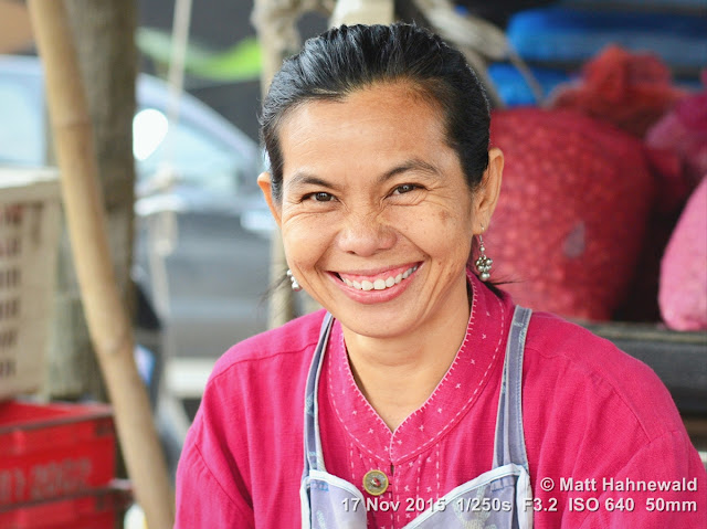 Matt Hahnewald; Facing the World; Asia; Northern Thailand; Chiang Dao; Tuesday market; people; closeup; portrait; street portrait; headshot; smiling; Thai woman; Thai smile; market woman; friendliness; Land of Smiles; world cultures; travel; tourism; eye contact; Nikon DSLR D3100; 50 mm prime lens; colour; face; market; outdoor