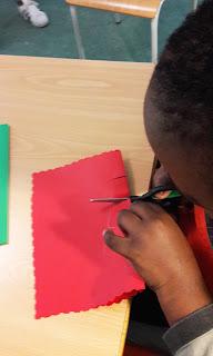Um aluno a cortar a cartolina vermelha para fazer o seu postal