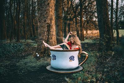 Chica rubia vestida de rojo dentro de una taza de café gigante en el bosque