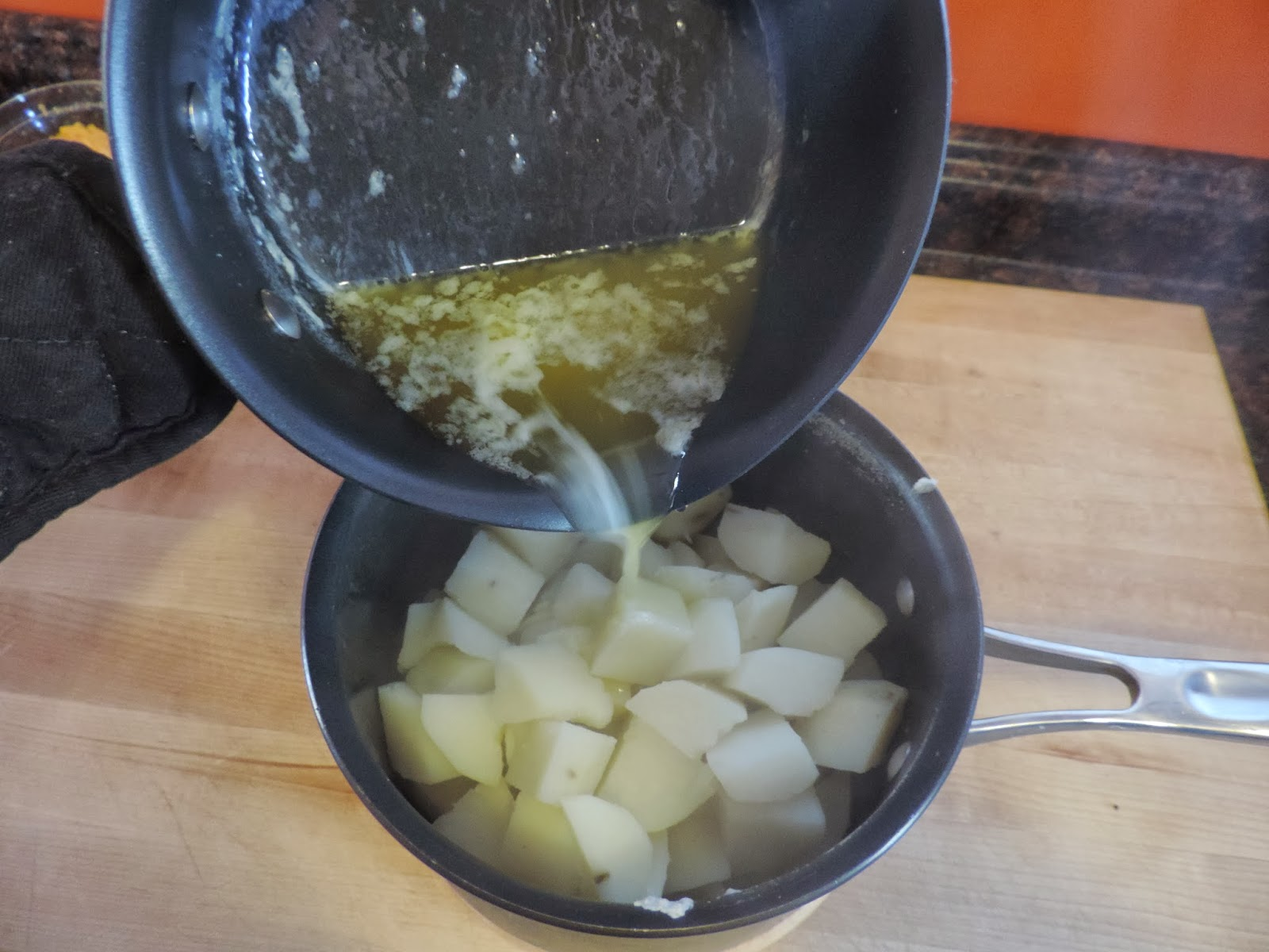 Melted Butter being added to the cooked potatoes in the sauce pan.