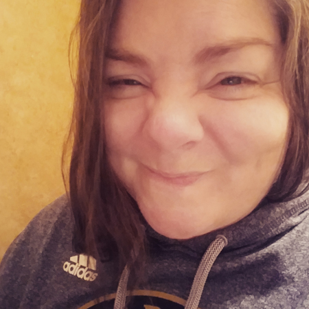 image of my face in close-up with a scrunched-up but happy expression; I am wearing a blue-grey hoodie and my hair is slightly damp
