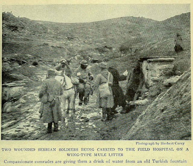 TWO WOUNDED SERBIAN SOLDIERS BEING CARRIED TO THE FIELD HOSPITAL ON A WING-TYPE MULE LITTER Compassionate comrades are giving them a drink of water from an old Turkish fountain