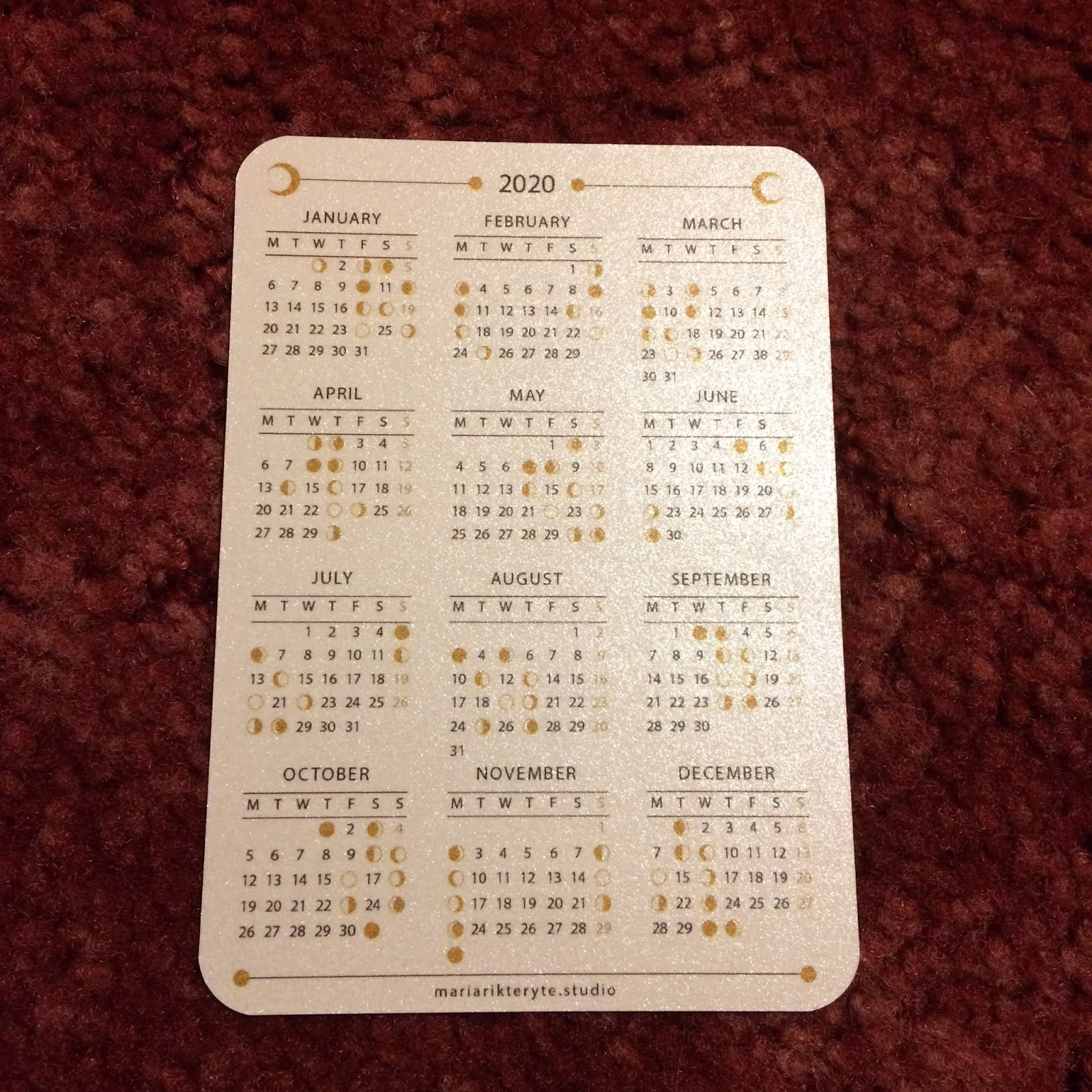 A playing card sized 2020 lunar calendar, showing the dates of different phases of the Moon in the UK in 2020
