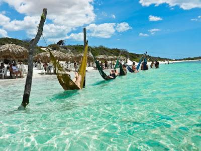 banhistas deitado na rede dentro praia - viagem das ferias