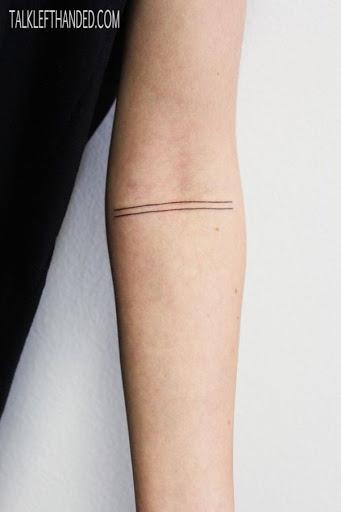 Duas finas linhas pretas são marcadas para o portador do antebraço neste tatuagem.