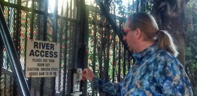 Jonathan L. Donihue swipes a card through an electronic reader device attached to a metal gate. A sign on the gate reads, 'RIVER ACCESS. Please use your room key. Caution: Uneven steps. Hours: 9 AM to 10 PM'