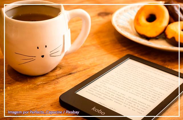 A imagem mostra uma mesa, em cima dela um leitor de livros digitais, ao lado do leitor, uma caneca com estampa de um rosto de um gato, ao fundo, um prato com biscoitos de chocolate