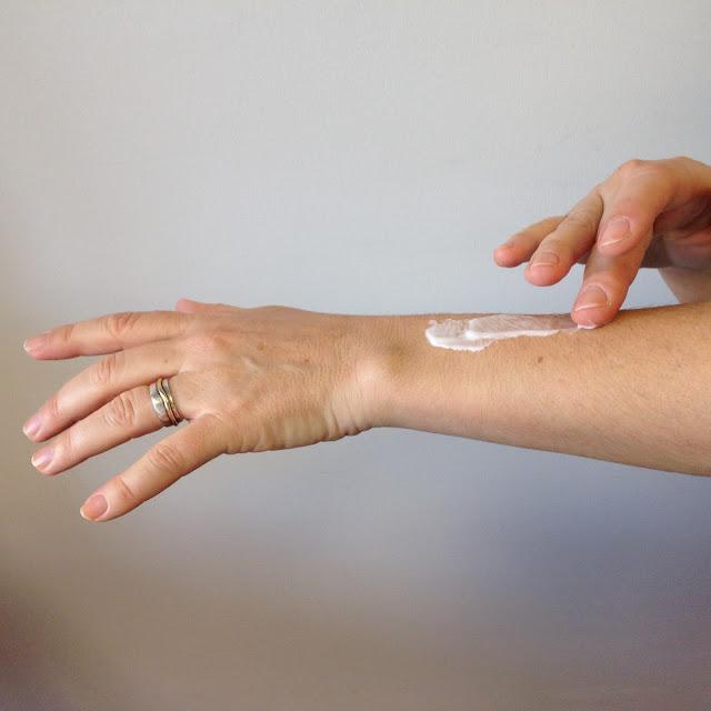 a espalhar no braço a loção corporal maximum relief