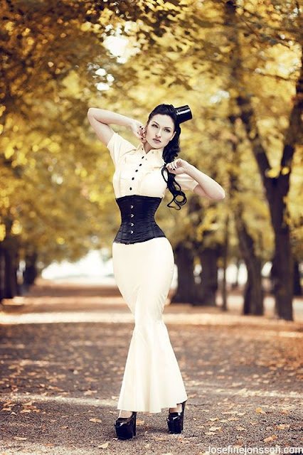 Simple and elegant steampunk outfit for women. White blouse and skirt with black underbust corset and mini top hat.