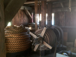 Very large coils of rope, piled several feet high, in a wooden building.