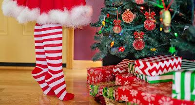 ragazza con calzini a righe e regali sotto l'albero