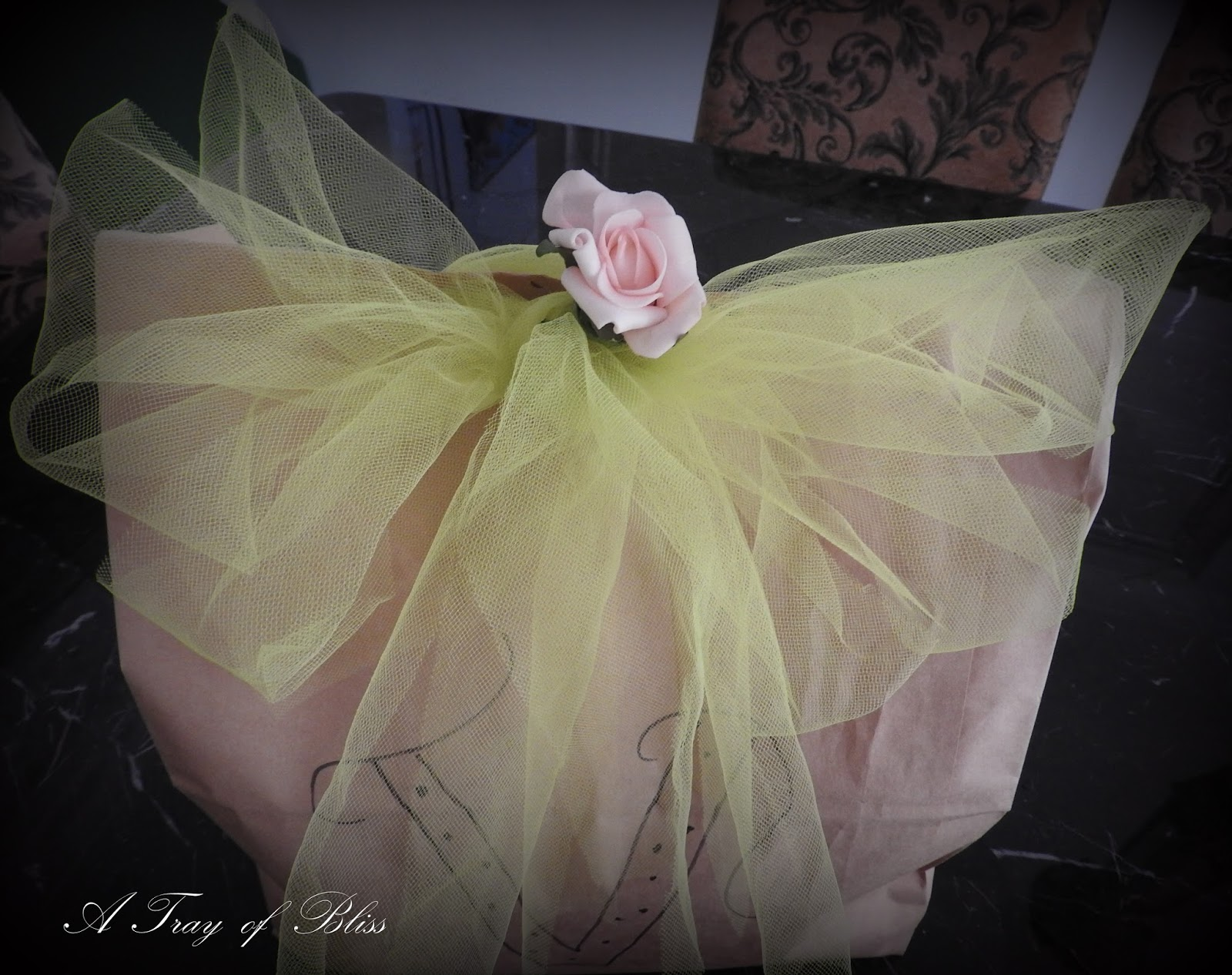 ...that lime green tulle ribbon, a peach rosebud, and brown paper.