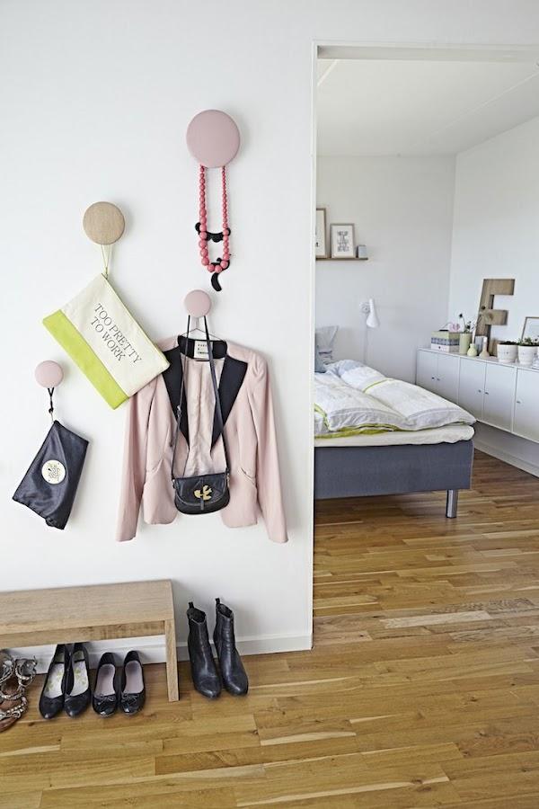 Dormitorio con colgadores tipo botón y banco zapatero