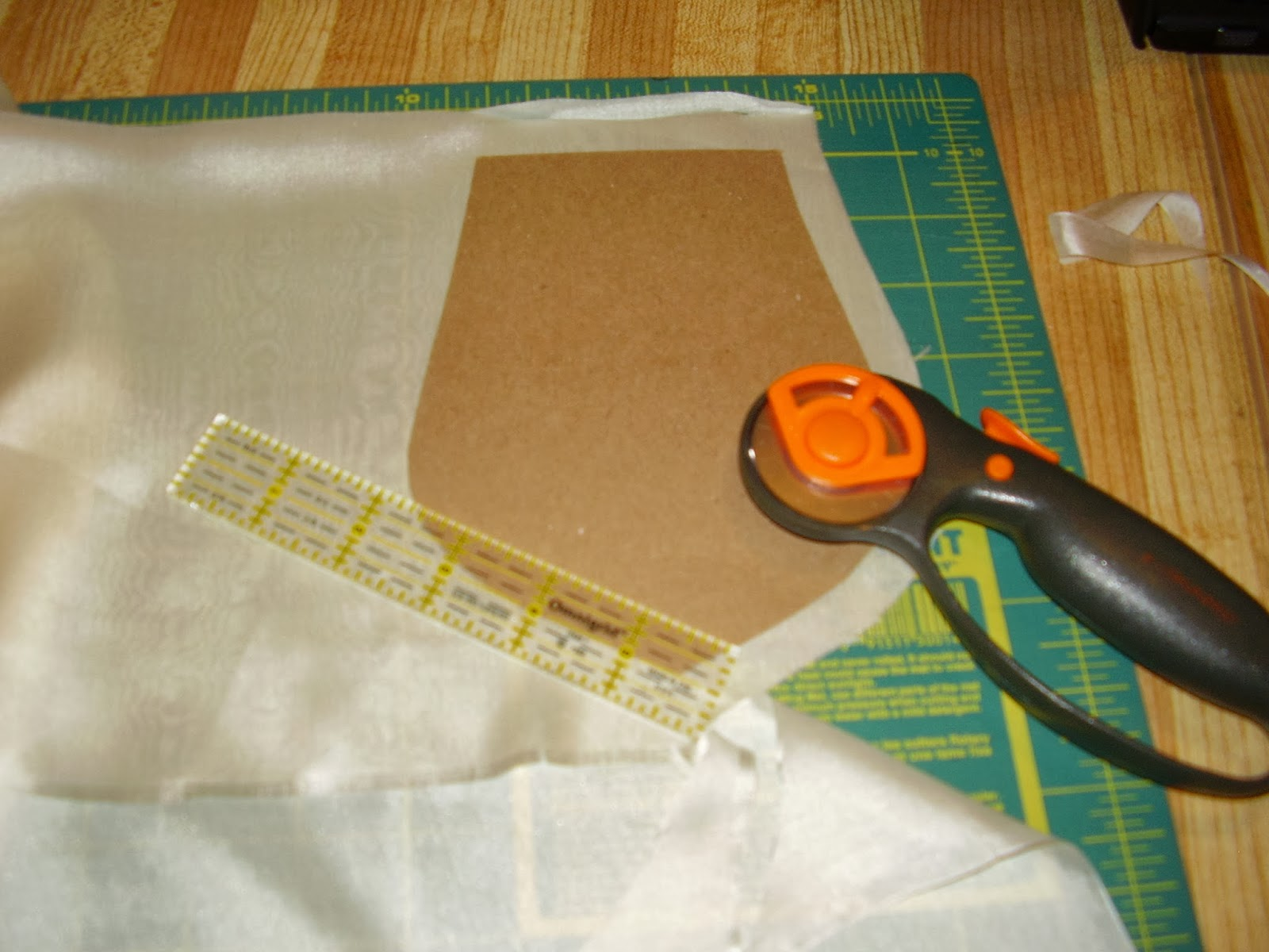 Cutting the silk from a cardboard pattern.