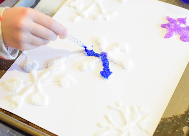 Salt Painted Snowflakes- fun winter process art activity for preschool, kindergarten, or elementary kids. Great for fine motor development, color theory, and science!