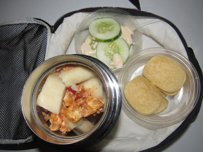 Nigerian school lunchbox meal of boiled yam with egg sauce and springle snack