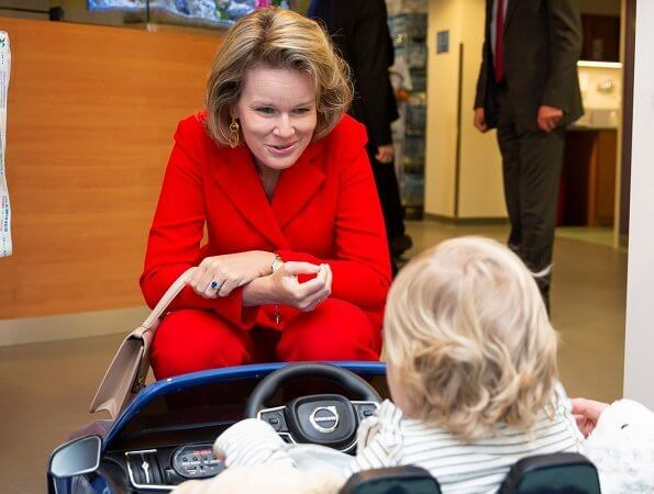Queen Mathilde visited Queen Fabiola Children's University Hospital. The Queen wore a double breasted orange blazer by Ralph Lauren