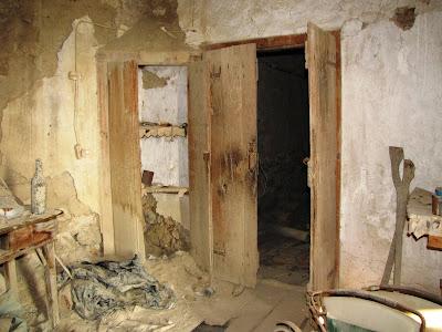 Η εσωτερική ξύλινη δίφυλλη διαχωριστική πόρτα μεταξύ των δύο θαλάμων του ισόγειου ορόφου με ένα επιτοίχιο ερμάριο ακριβώς δίπλα της