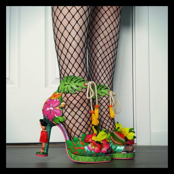 legs wearing fishnet tights and colourful fruit flower shoes with hula girl heels